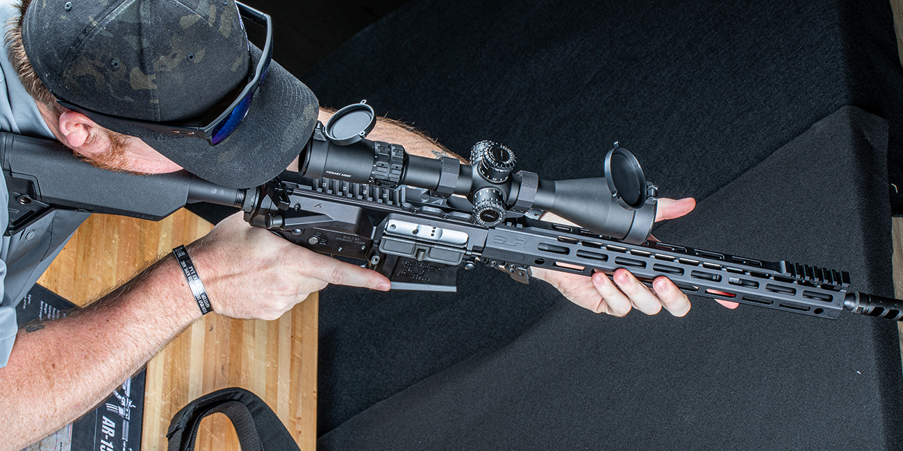 Aiming down a rifle scope mounted on an AR 308 built by Primary Arms