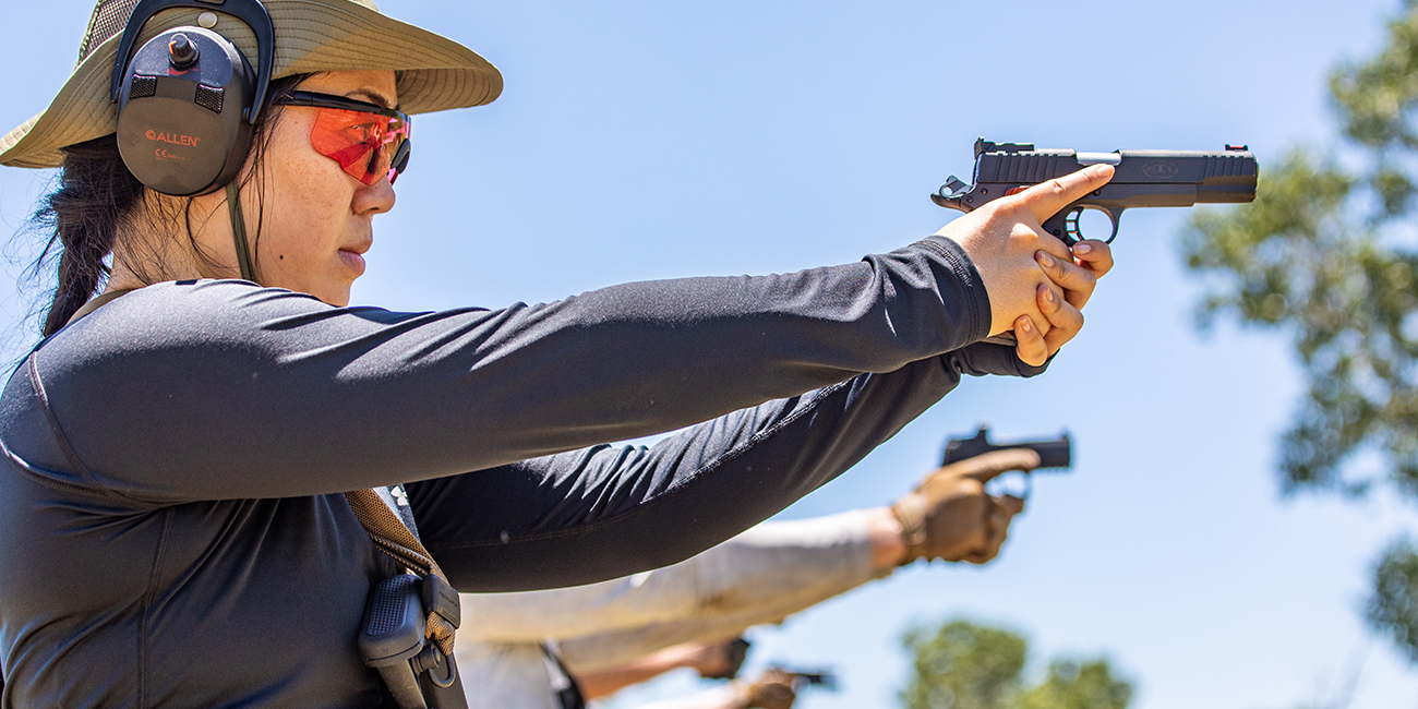 Woman points STI 1911 pistol downrange during training course