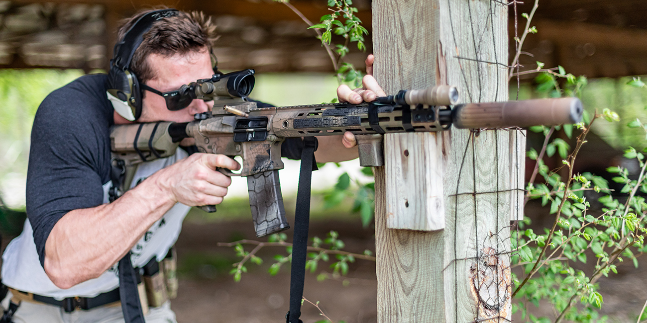 Shooter with AR15 and BCM short vertical foregrip braces rifle against wooden pillar for accurate shooting