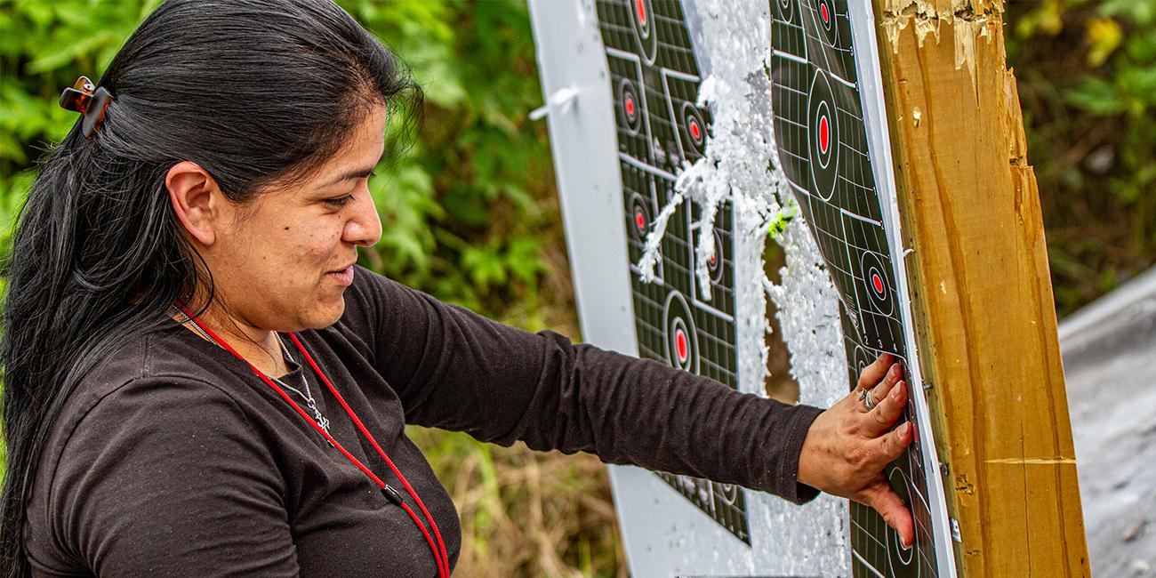 Woman sets up rifle target on wood backboard at gun range