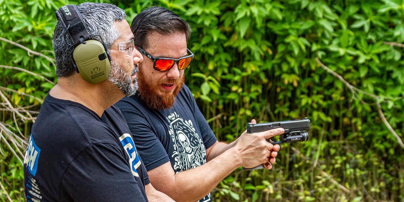Instructor in sunglasses demonstrates proper grip on 9mm glock handgun