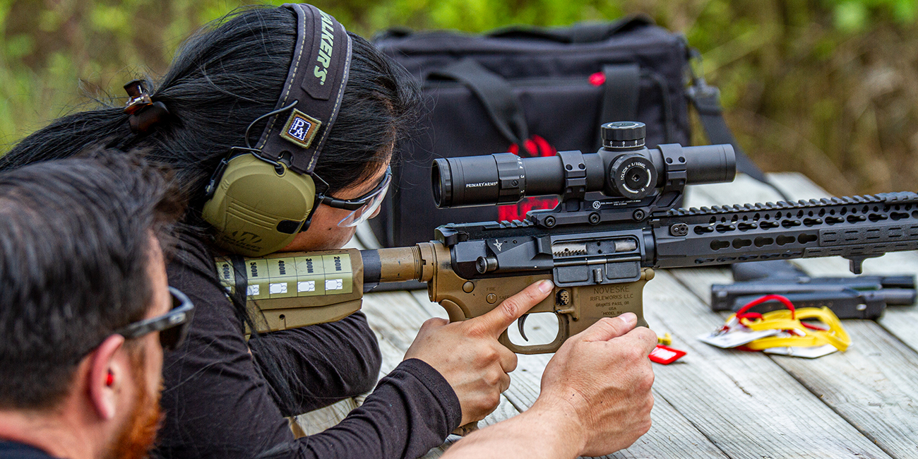 Man and Woman practice gun safety on AR 15 with Primary Arms Platinum 1-8x24 First Focal Plane Rifle Scope