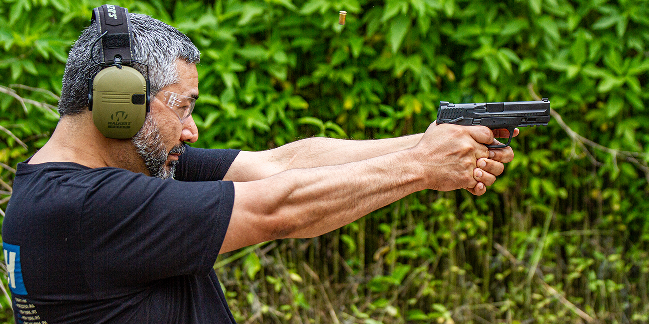Man aims down the sights of a Smith and Wesson M&P 9mm Handgun