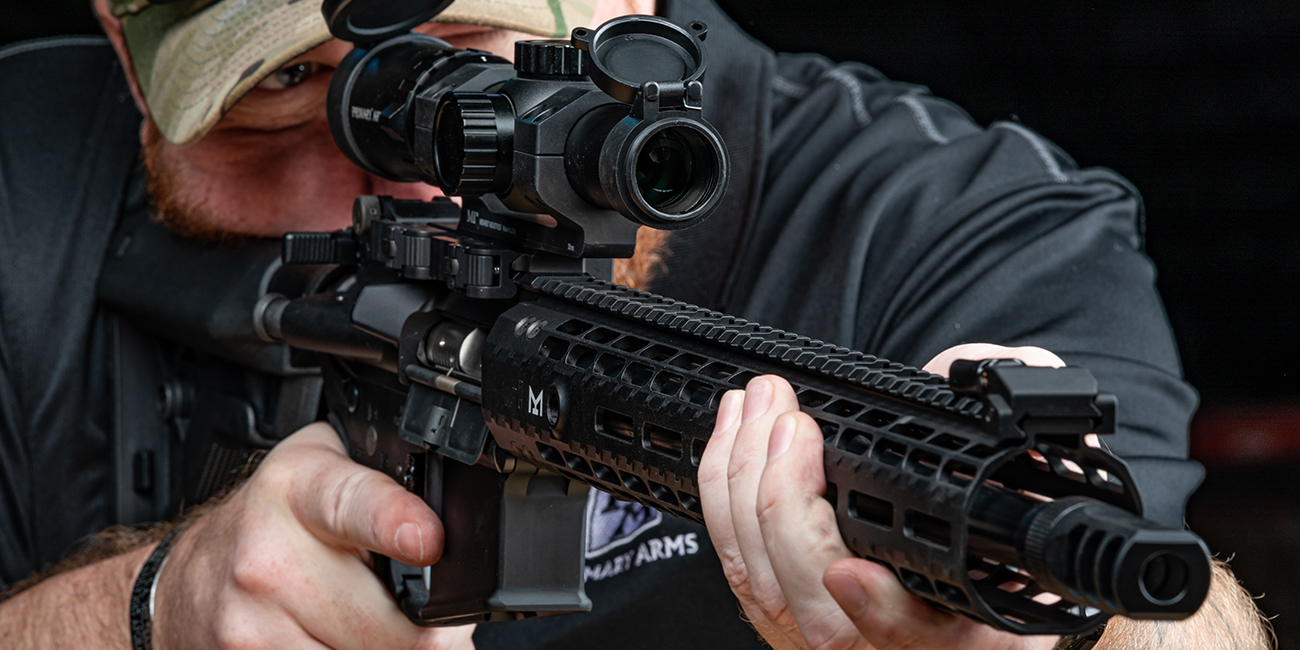 Shooter looks down a Primary Arm rifle scope while preparing to fire a .458 SOCOM ar rifle
