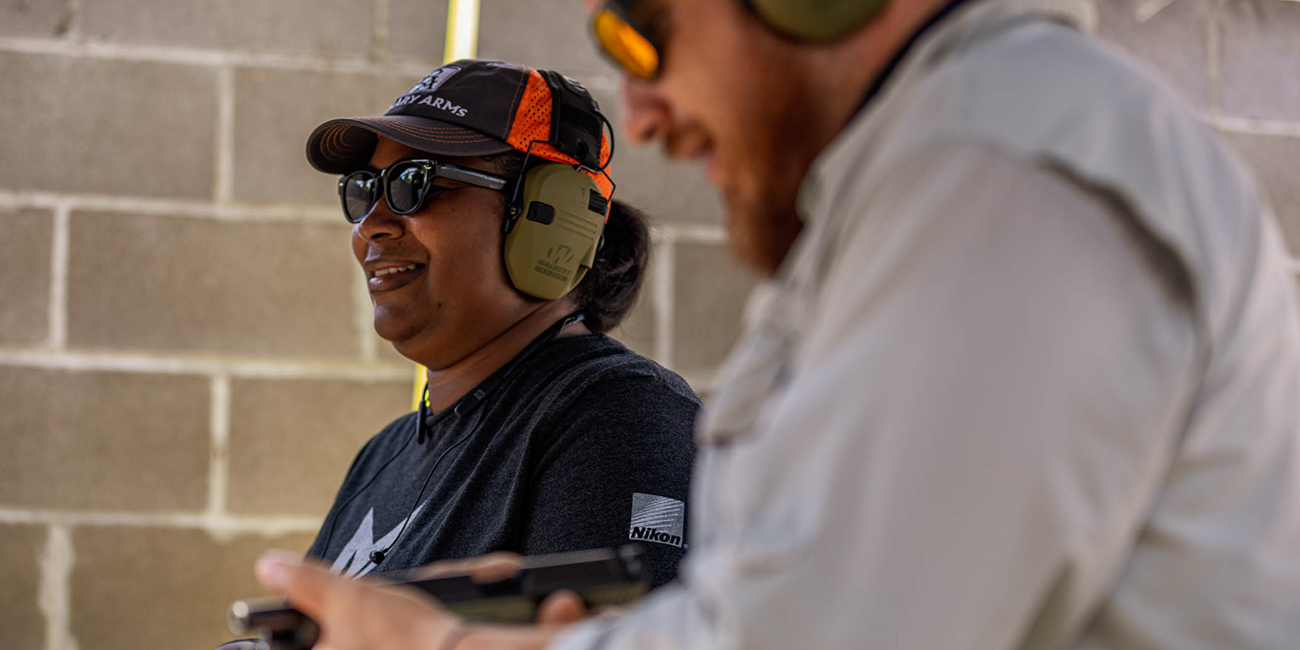 New shooter, Dea, smiling at her first range trip while her instructor checks a Glock handgun.