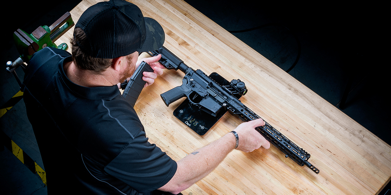 Gunsmith weighing lightweight ar15 rifle for Primary Arms free rifle giveaway
