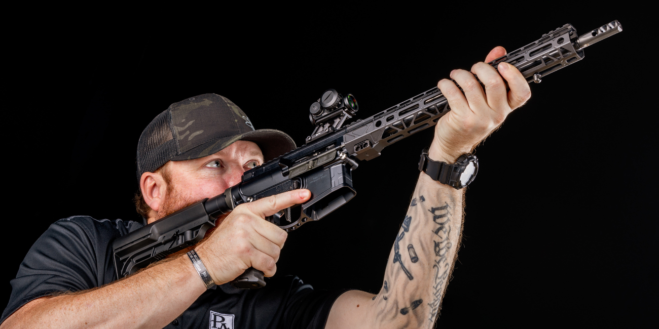 Gunsmith shouldering lightweight giveaway rifle and looking down Primary Arms microdot sight
