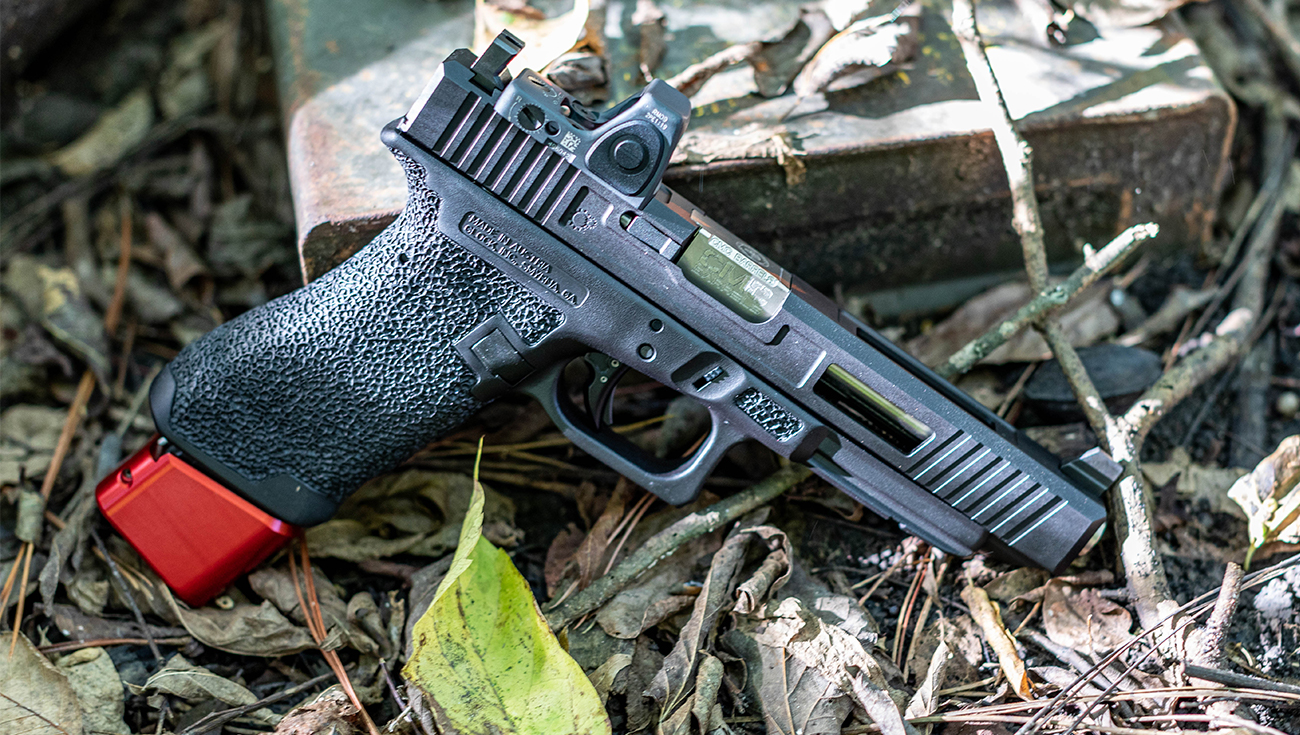 Glock 34 Longslide 9mm Giveaway Pistol resting in a bed of twigs and leaves