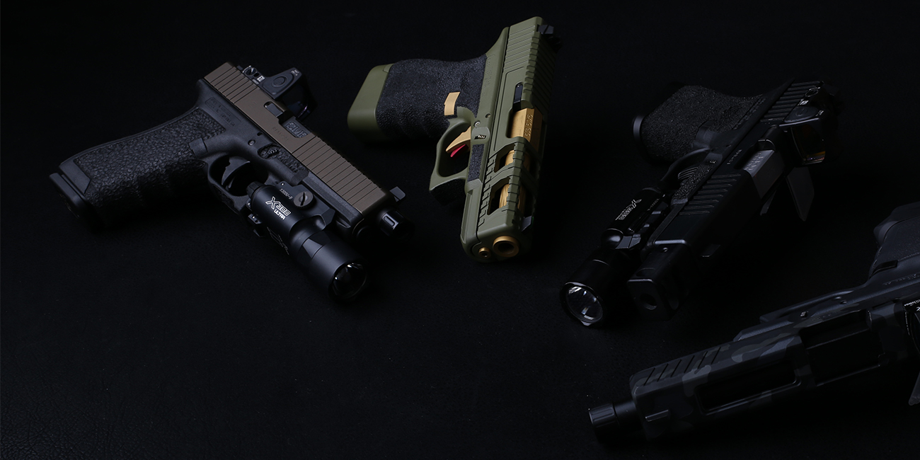 Four different customized Glock handguns with Surefire, Trijicon, and CMC Triggers parts