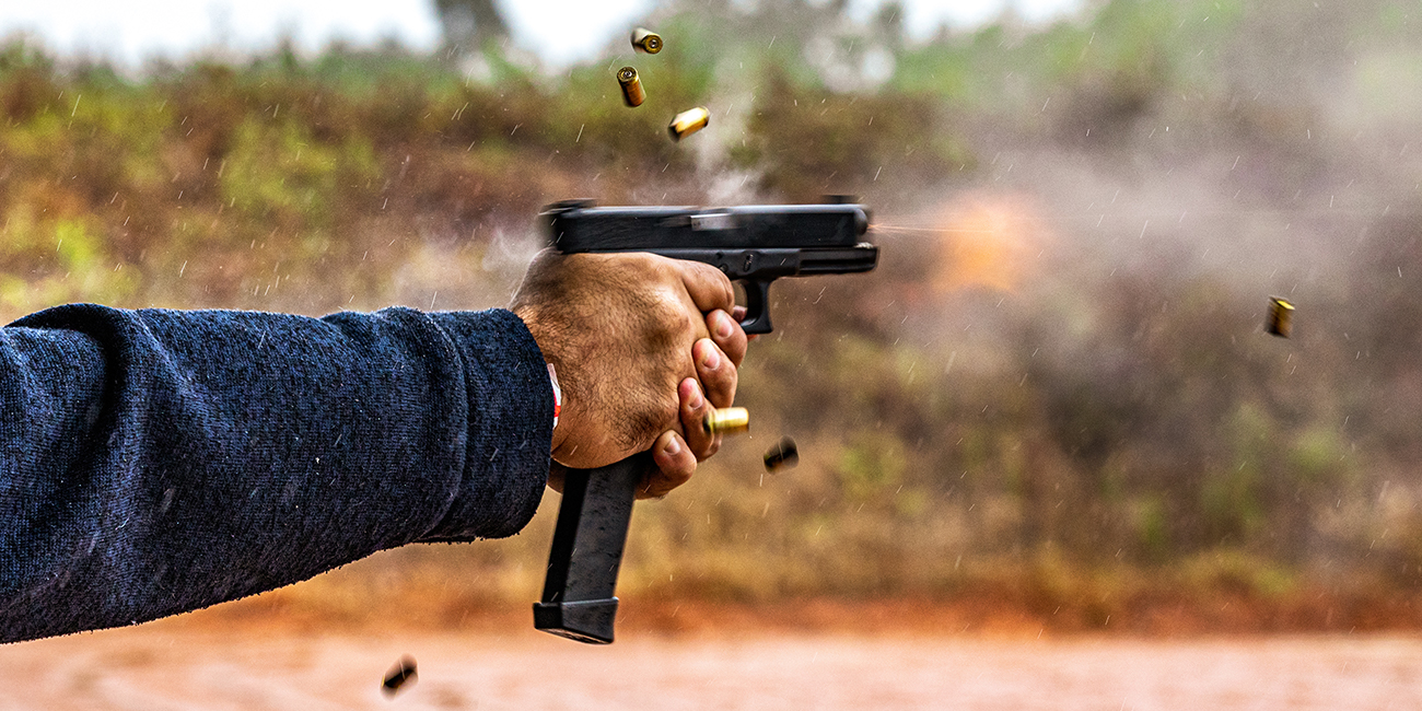 Glock 18 fires off a burst of 9mm in the rain at a range day event