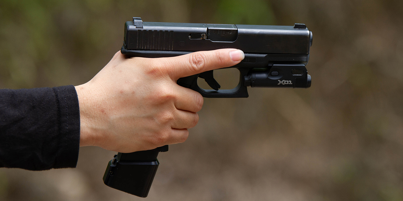 Side view of a Glock 19 9mm handgun with Surefire XC1 weaponlight and extended magazine baseplate