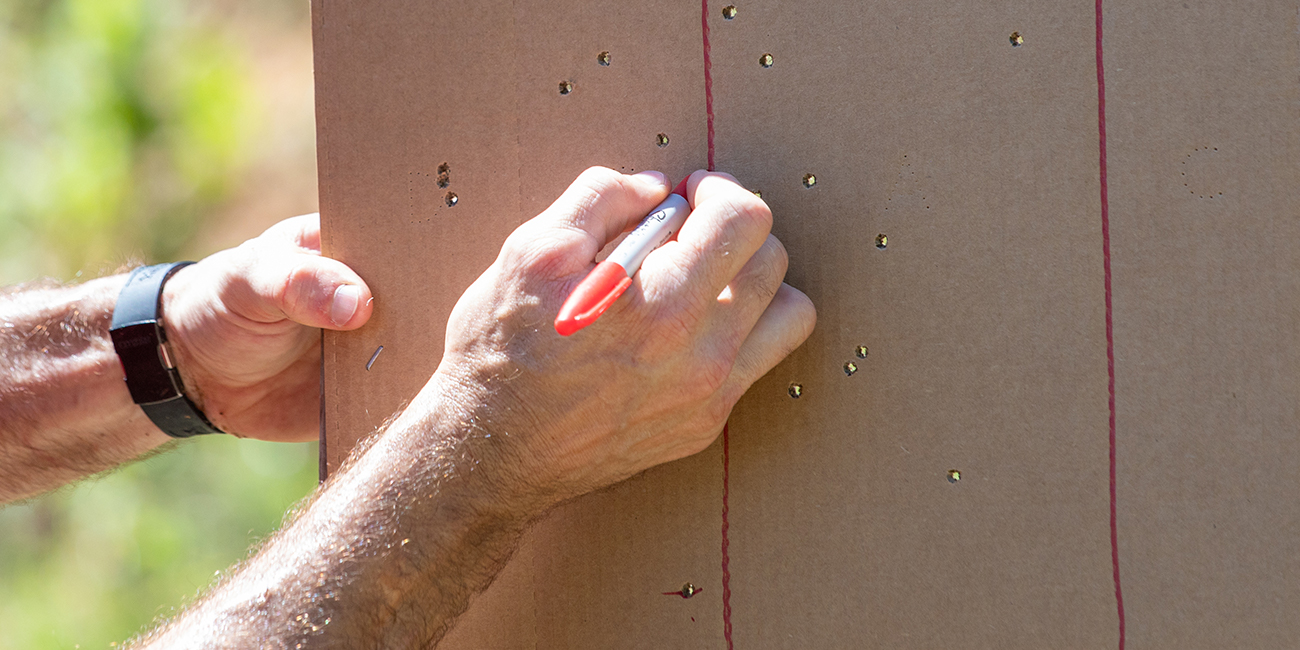 Instructor circles hit and miss marks with a Sharpie on a standard IPSC silhouette
